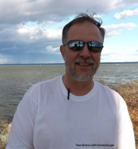 A white male with a graying beard is standing in front of what appears to be a lake, smiling . He has on a white t-shirt and mirrored sunglasses that show the reflection of someone taking his photograph. Under his t-shirt is a pen clipped to his collar.