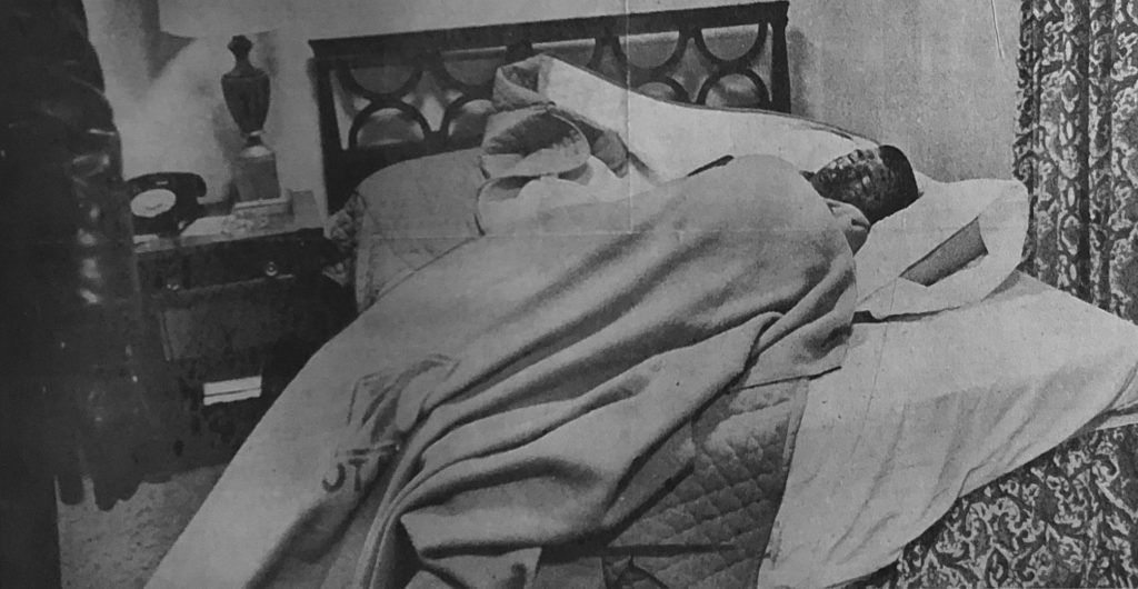 A black and white photo of Charles Bright wrapped up in blankets on a hotel bed after his fall.