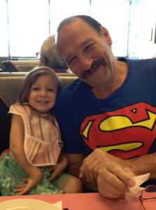 A balding white man smiles as he wears a Superman t-shirt. To his right is a little girl, his granddaughter.