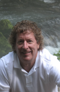 A brown curly-haired man sits in front of a moving river.