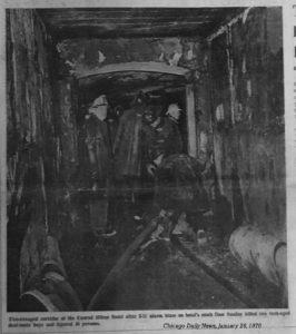 B+W photo of firemen looking at charred corridor