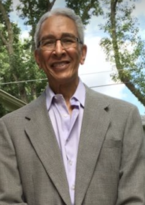 A brown-skinned man in a suit jacket and purple button-down shirt is smiling, his hair gray, in front of a blue cloud-filled sky and trees.