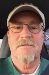 A white man is in his car, looking at the camera. He has a blonde/grayish goatee, glasses, and a baseball cap on.