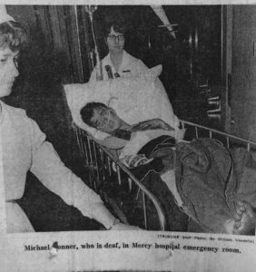 Michael Tonner is shown in a hospital gurney surrounded by two nurses.