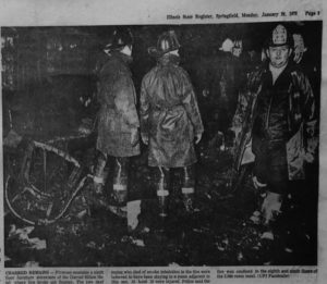 Firemen examine the room where the fire is suspected to have started.